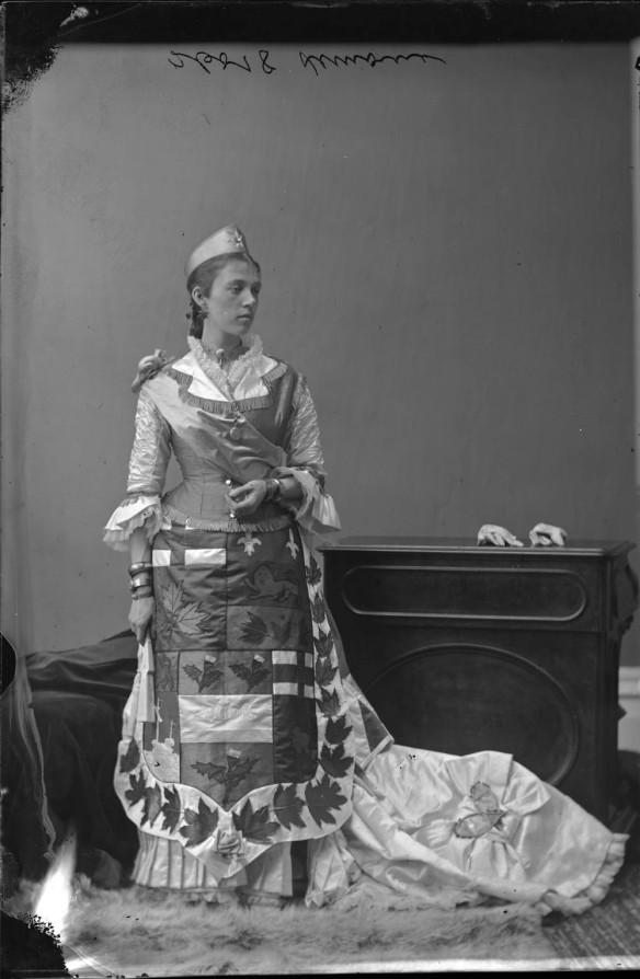 Photo noir et blanc d'une femme costumée en Dominion du Canada dans un studio de photographie. Sur le devant de sa robe, on aperçoit les armes du Dominion entourées de feuilles d'érable brodées. Des raquettes miniatures se trouvent sur la traîne de sa robe.