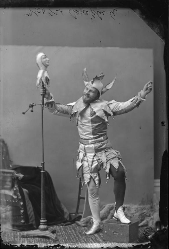 Photo noir et blanc d'un homme costumé en fou du Roi prenant la pose dans un studio de photographie. Il tient une marionnette sur pied dans sa main droite.