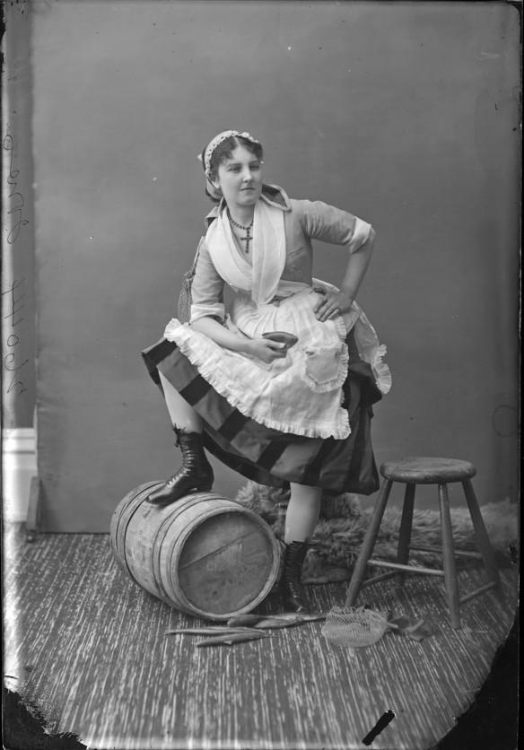 Photo noir et blanc d'une jeune femme costumée en poissonnière et prenant la pose dans un studio de photographie. Sa main gauche est posée sur sa hanche, sa main droite tenant un poisson en papier mâché et son pied droit soulevé, appuyé sur un baril en bois.