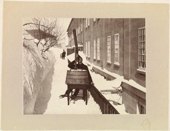 Photographie noir et blanc d'un homme assis à une table à l'extérieur en hiver et observant le ciel à l'aide d'un télescope.