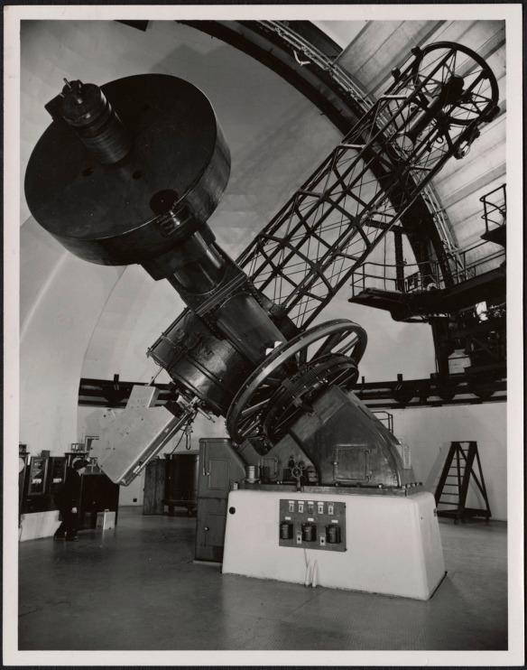 Photographie noir et blanc d'un homme regardant dans l'oculaire du télescope de l'Observatoire fédéral d'astrophysique à Victoria.