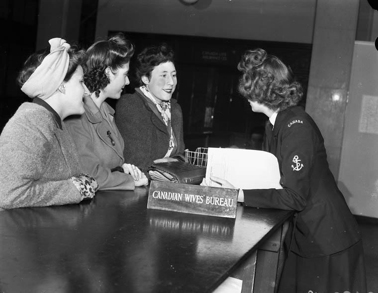 Photographie en noir et blanc d'une femme en uniforme militaire qui s'appuie sur un comptoir pour interviewer trois femmes, à côté d'un écriteau qui indique « Canadian Wives' Bureau ».