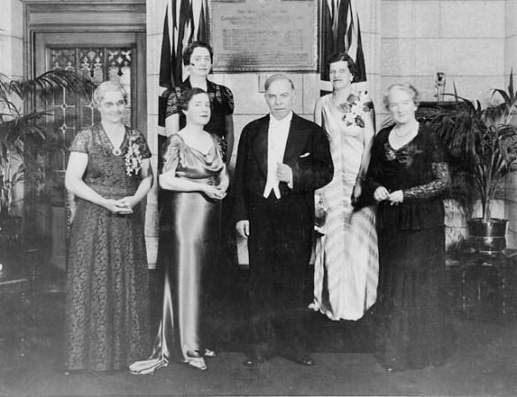 Cinq femmes vêtues d'une robe de soirée ornée d'une boutonnière et un homme en smoking. Tous sont debout devant une plaque.