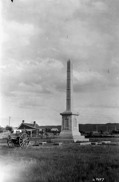 Photo en noir et blanc d'un obélisque avec un chariot sur roues à proximité.