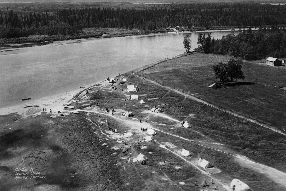 Photographie aérienne en noir et blanc d'une rive avec des routes étroites, des tentes et des gens qui marchent. À droite, il y a des arbres et un bâtiment qui ressemble à une grange.