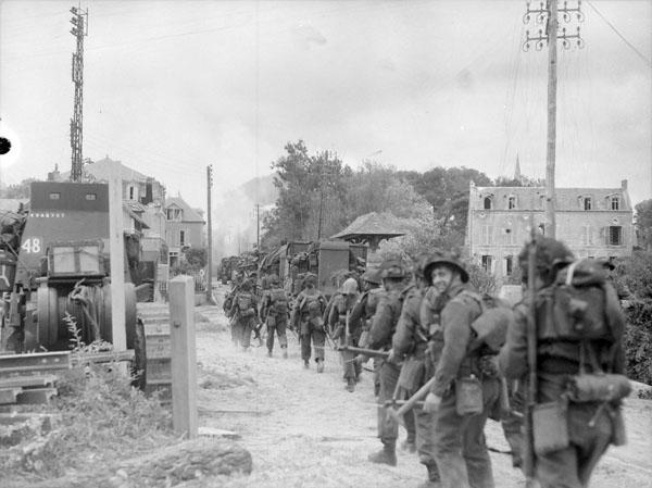 Photo noir et blanc d'une file de soldats marchant dans une rue au milieu d'un village touché par les combats.