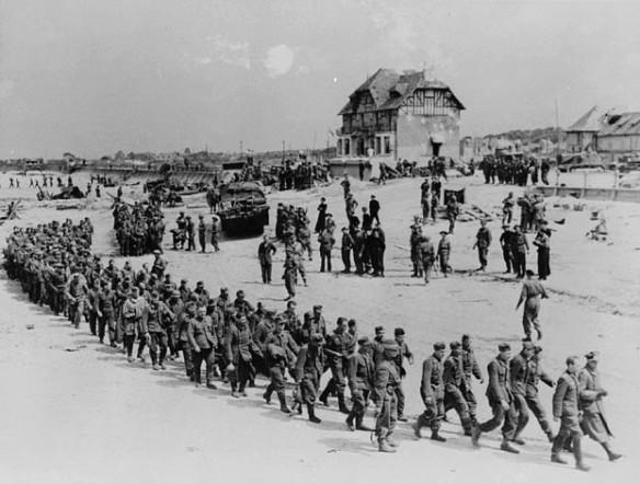 Photo noir et blanc montrant une longue file de soldats allemands marchant sur une plage, dirigés par des soldats alliés. On aperçoit à l'arrière-plan des véhicules, une digue et une grosse maison.