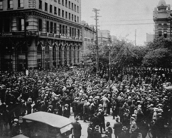 Photo noir et blanc de grévistes envahissant une rue devant un imposant édifice.