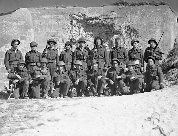 Photo noir et blanc de matelots en tenues de combat. Ceux du premier rang sont agenouillés tandis que leurs collègues au deuxième rang sont debout, devant une fortification en béton endommagée.