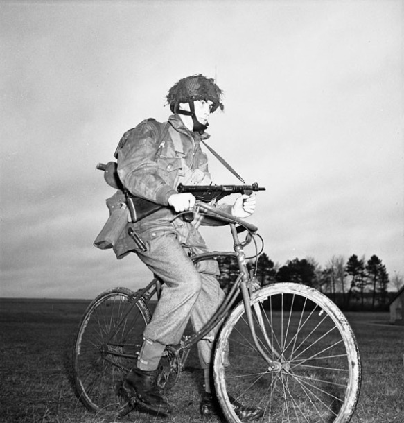 Photo noir et blanc montrant un soldat assis sur un vélo dans une clairière. Il porte une vareuse de parachutiste et tient une mitraillette Sten.