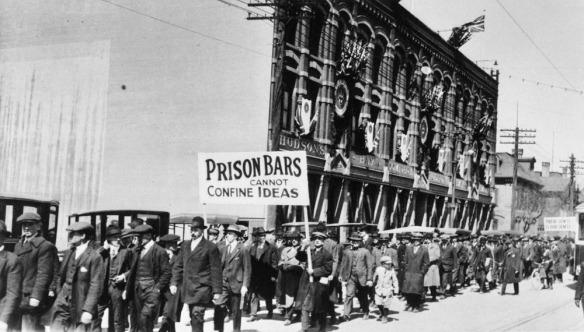 Photo noir et blanc de manifestants dans la rue, avec une pancarte sur laquelle est inscrit « Prison bars cannot confine ideas [Les barreaux d'une prison n'enferment pas les idées] ».