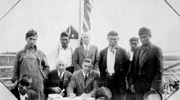 Une photographie en noir et blanc où des hommes des Premières Nations et des représentants du gouvernement posent devant des documents du traité, avec un drapeau en arrière-plan.