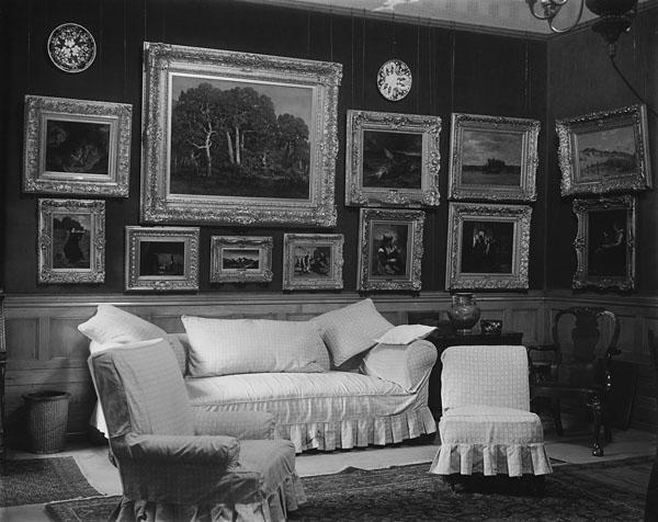 Photo noir et blanc d'un salon meublé de fauteuils confortables, de peintures et d'un divan