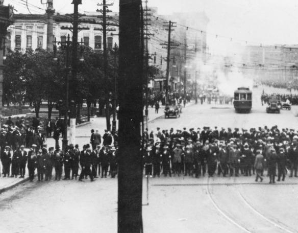Photo noir et blanc d'un tram d'où s'échappe de la fumée, avec des spectateurs amassés à l'avant-plan.