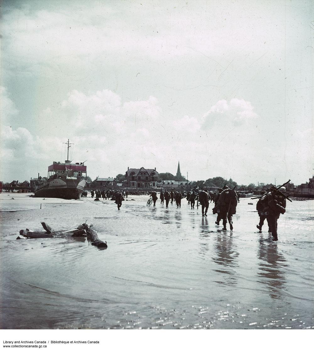 Photo couleur de soldats chargés d'armes et d'équipement, marchant dans de l'eau peu profonde en direction d'un village français.