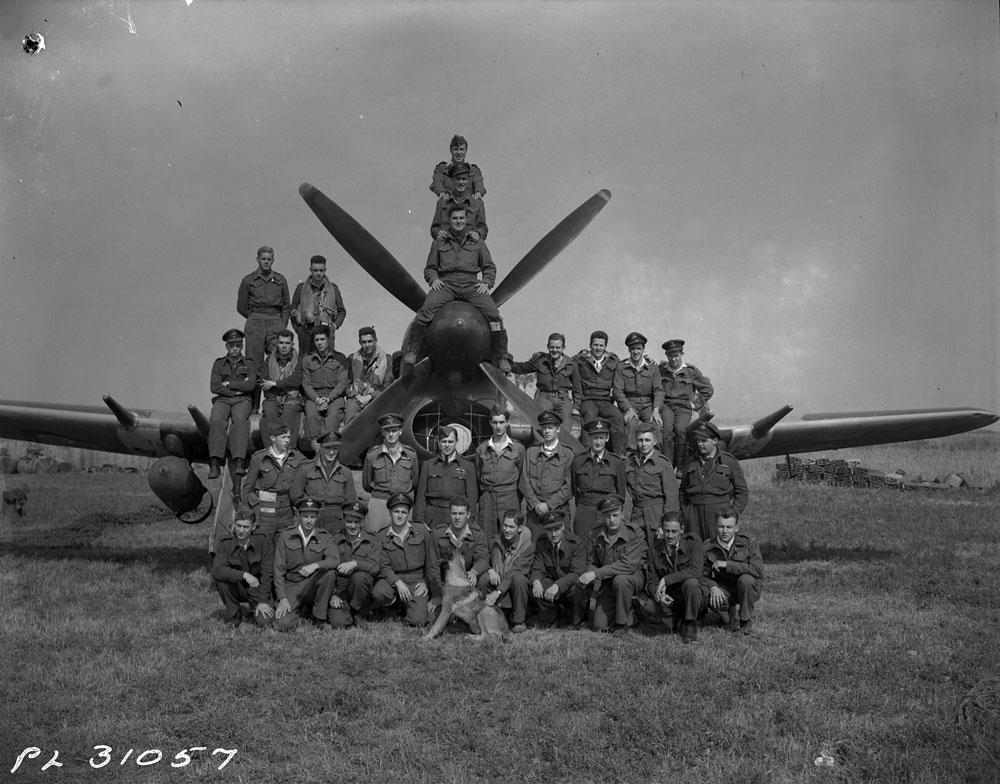Photo noir et blanc d'un escadron de l'Aviation royale canadienne posant autour d'un chasseur-bombardier équipé d'une grosse bombe.