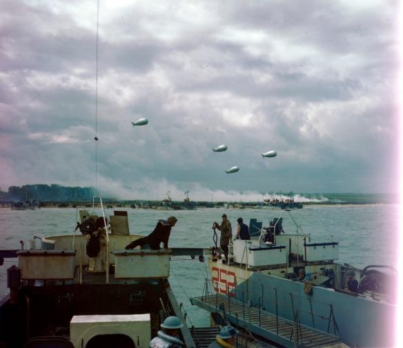 Photo couleur d'une péniche de débarquement s'approchant d'une plage. Sur la rive, on distingue un village d'où s'élève de la fumée. Dans le ciel, des dirigeables assurent la défense aérienne.