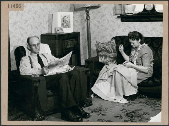 Photo noir et blanc d'un homme assis dans un fauteuil et lisant un journal; une femme est assise sur un divan et coud.
