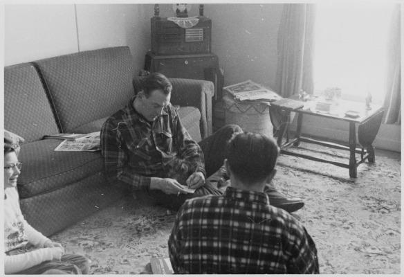 Photo noir et blanc d'un homme assis sur un petit tapis avec des amis; adossé contre un divan, il fume une cigarette et écrit dans un carnet