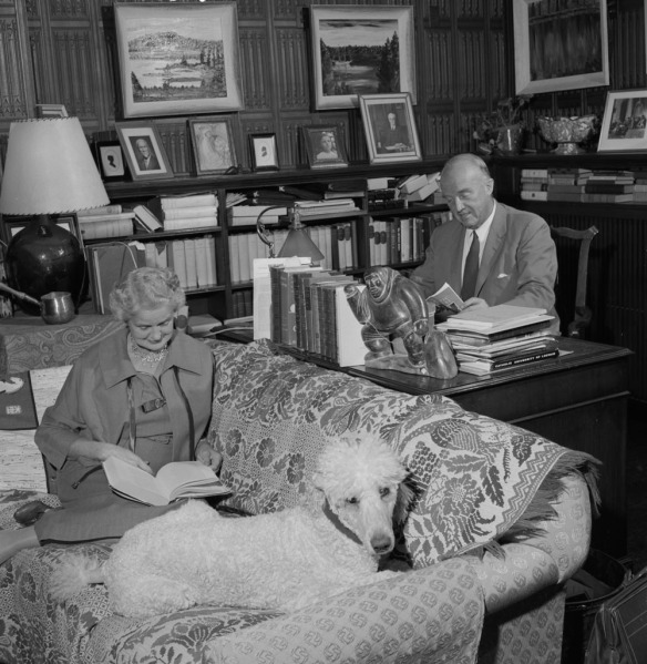 Photo noir et blanc d'une femme assise sur un divan, lisant un livre près de son caniche; un homme assis tout près à son bureau lit un magazine