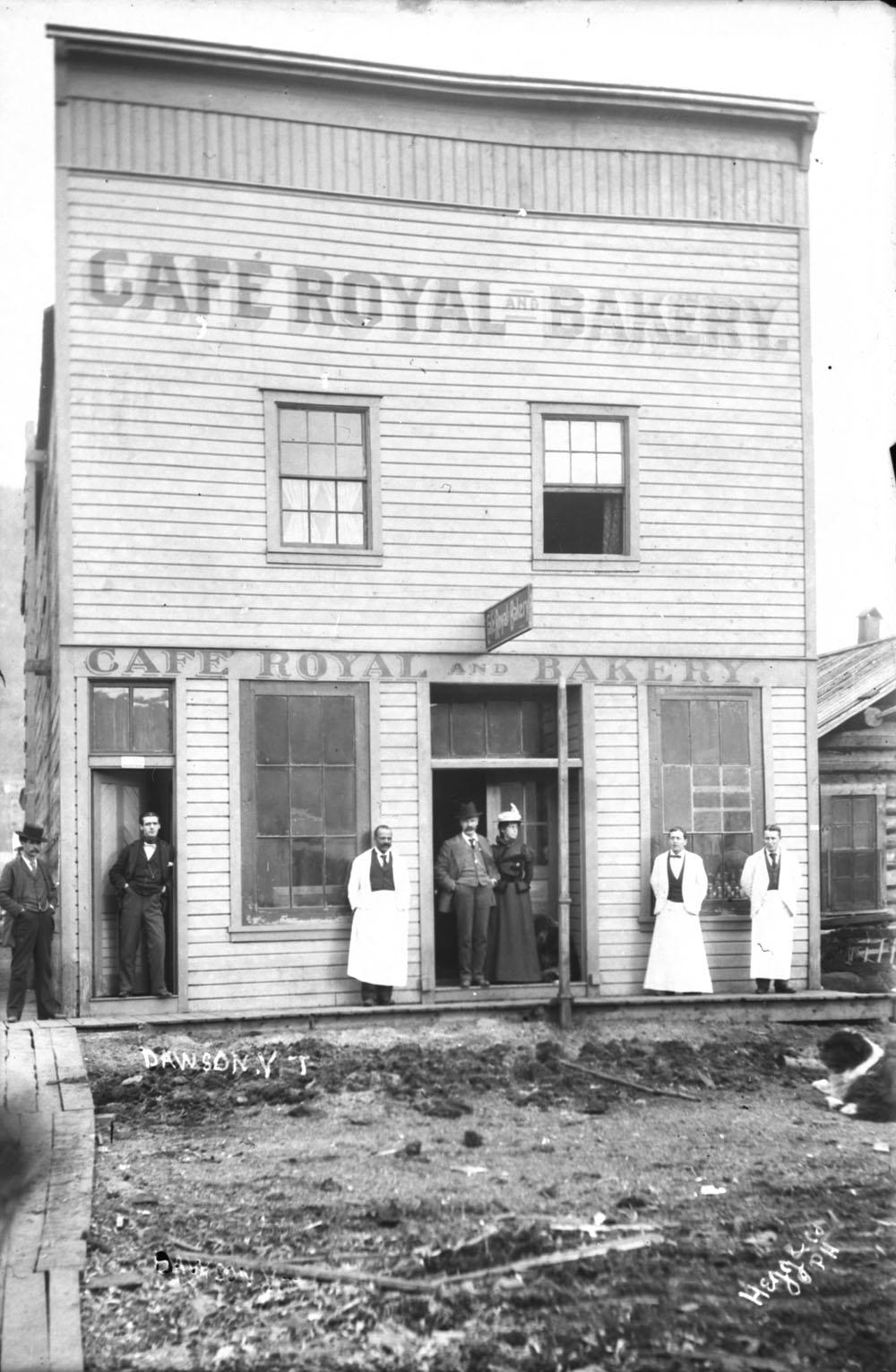 Un bâtiment en bois porte la mention « Café Royal and Bakery ». Trois serveurs et quatre clients se tiennent debout sur le trottoir de bois, devant le bâtiment.
