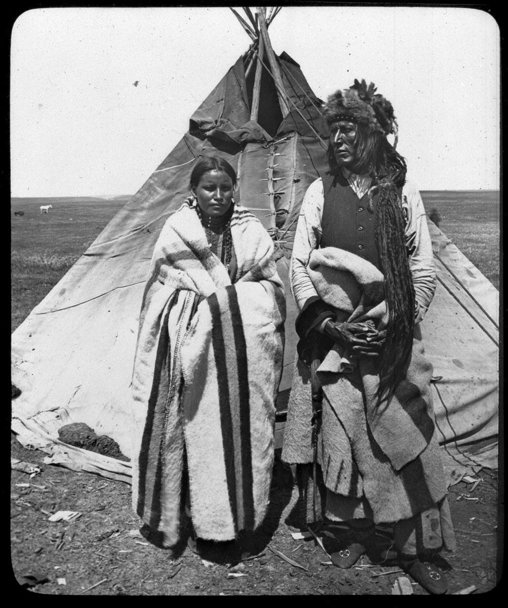 Photographie en noir et blanc de Poundmaker debout devant un tipi avec un bonnet de fourrure, une chemise, une veste, une couverture autour de la taille et des mocassins. Sa femme se tient à ses côtés, vêtue d'une robe et d'une couverture jetée sur les épaules