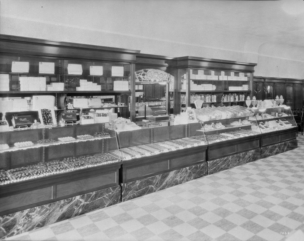 Quatre vitrines garnies de produits de boulangerie-pâtisserie forment un long comptoir. De grandes tablettes en bois avec un miroir au milieu sont recouvertes de boîtes. Le plancher présente un motif en damier.