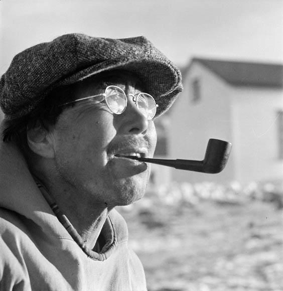 Portrait rapproché d'un homme fumant la pipe et portant une casquette plate et des lunettes rondes.