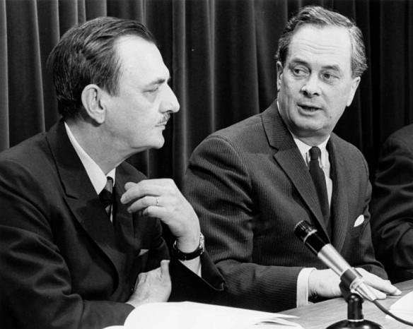 Une photo en noir et blanc montre deux hommes avec un microphone entre les deux.