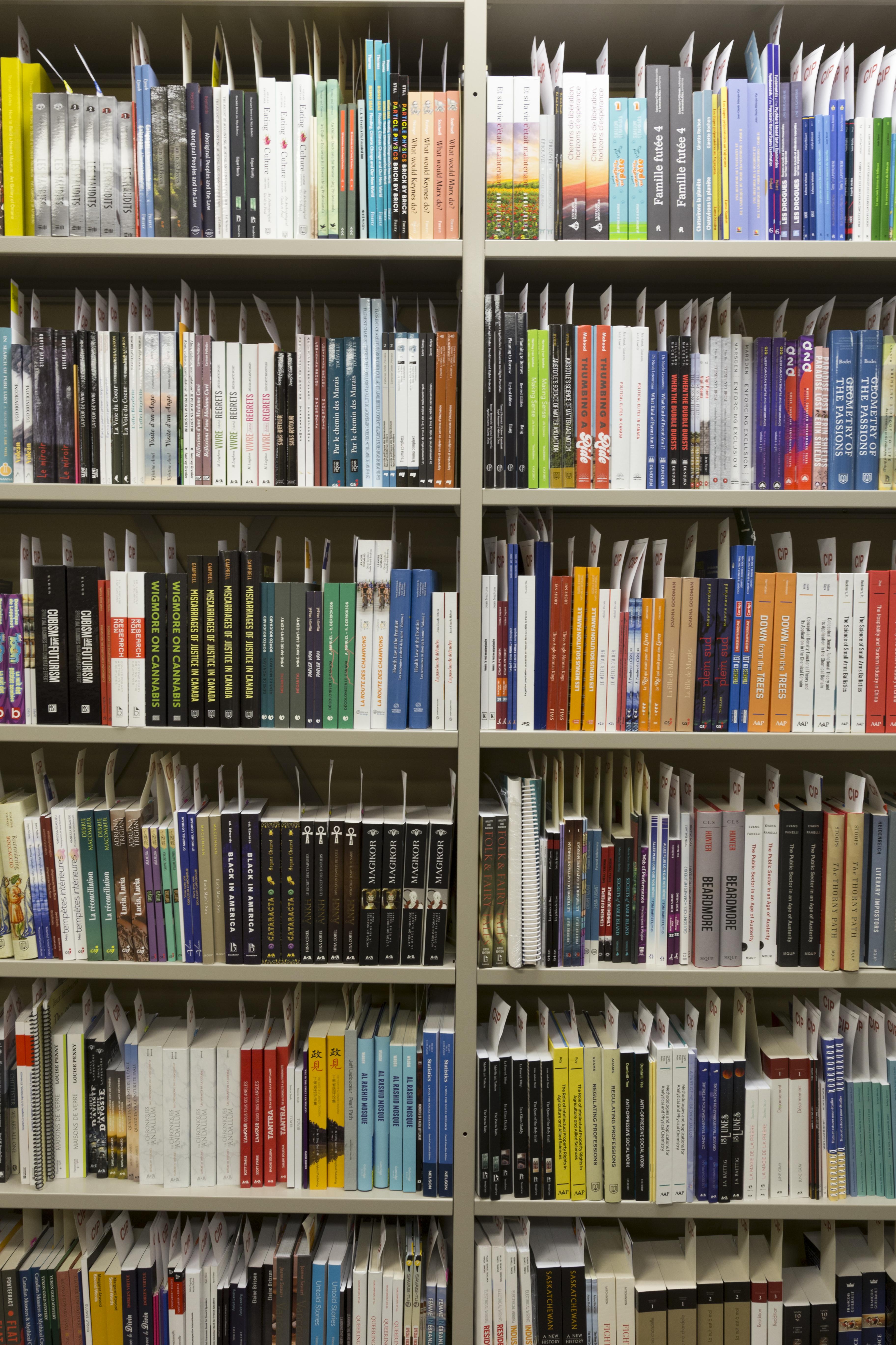 Des rangées de livres aux couvertures multicolores, prêts à être traités, reposent sur des étagères en métal gris.