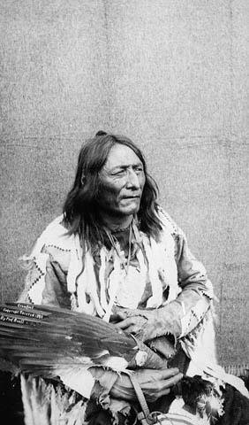 Photographie en noir et blanc d'Isapo-Muxika (Pied-de-Corbeau) assis, tenant un éventail en plumes d'aigle et portant une chemise de peau ornée de fourrure et de perles ou de plumes.