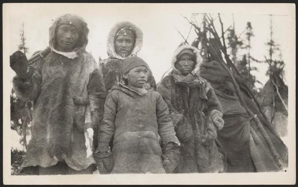 Une photographie noir et blanc d'un Innu avec trois membres de sa famille. Les hommes et un jeune garçon portent un manteau et des mitaines en fourrure. Il y a une tente et des arbres à l'arrière-plan.
