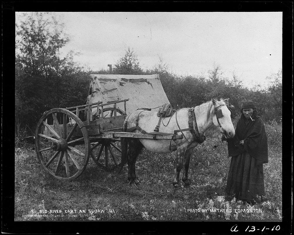 Femme fumant la pipe vêtue d'une robe, d'un châle et d'un bandana; elle tient les rênes d'un cheval tirant une charrette de la rivière Rouge.