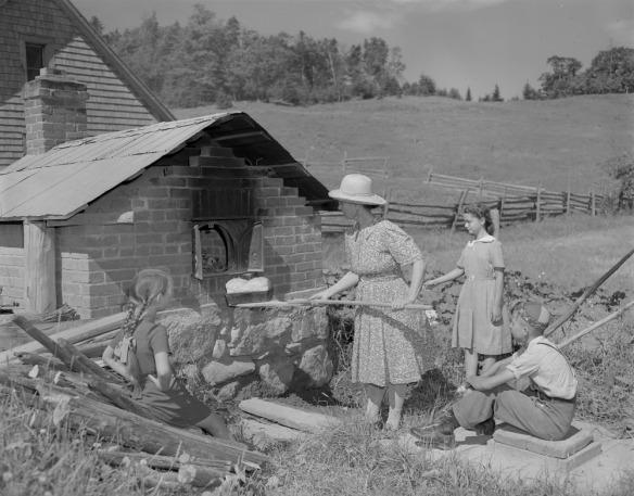 Trois enfants regardent leur mère qui retire un pain d'un four extérieur en brique. À l'arrière-plan, on peut voir une maison et un champ.