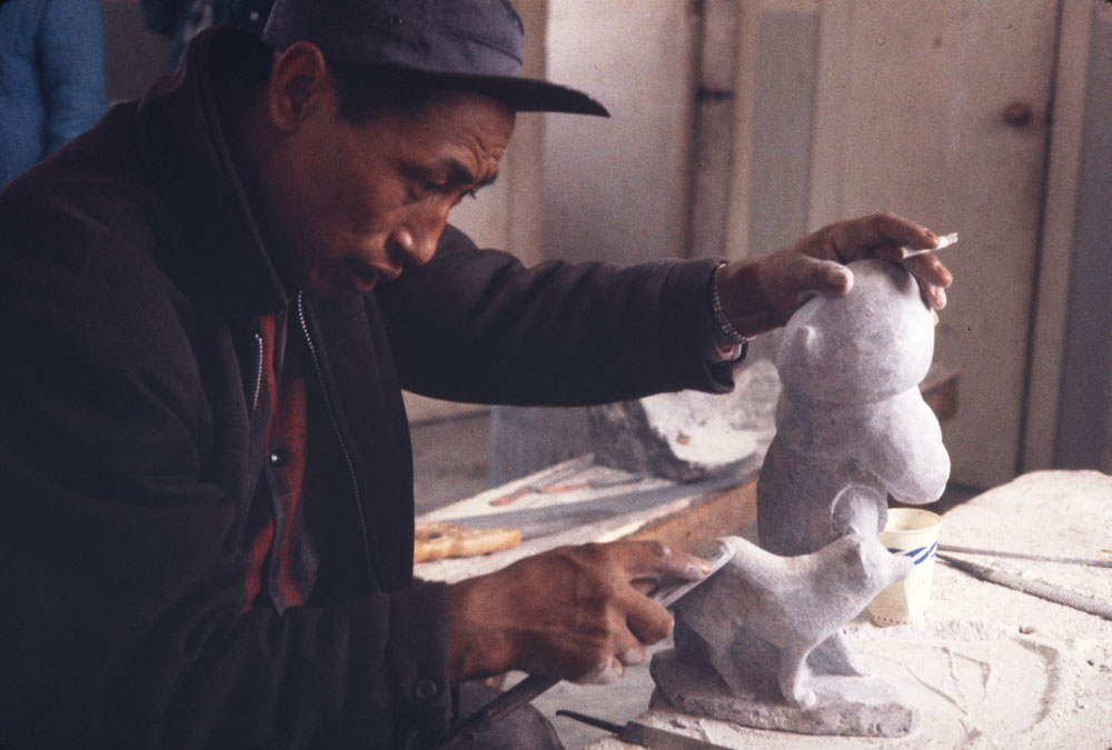 Photographie couleur d'un homme inuit portant une veste et une casquette foncées, en train de sculpter des statues blanches.