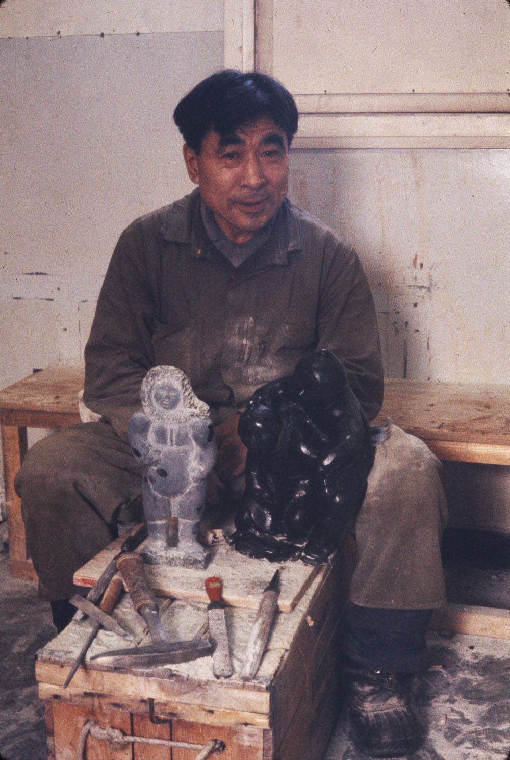 Photographie couleur montrant un homme inuit assis derrière une sculpture de pierre et des outils.