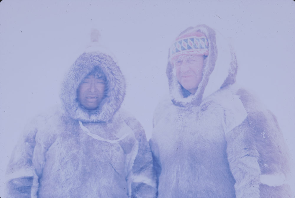 Photographie couleur de Kove, un Inuit, et de Charles Gimpel, tous deux vêtus d'une parka en fourrure brun et blanc. La photo est très floue à cause d'une tempête de neige.