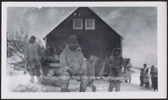 Une photographie noir et blanc d'un Innu regardant l'appareil photo, vêtu de vêtements traditionnels et assis sur une pile de provisions. À l'arrière-plan, plusieurs personnes se tiennent debout devant une maison de couleur foncée percée de deux petites fenêtres.