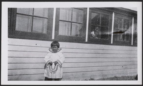 Photographie noir et blanc d'une Inuite faisant face à l'appareil photo. La jeune fille porte un amauti blanc (un manteau de femme ou de fille muni d'un grand capuchon) et se tient devant un bâtiment, tandis qu'une femme regarde par une fenêtre derrière elle.