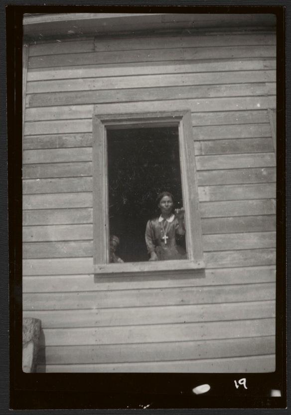 Une photographie noir et blanc d'une femme debout à la fenêtre d'un bâtiment en bois, portant une robe avec un collet blanc et une chaîne ornée d'une grande croix. Dans le coin inférieur gauche de la fenêtre, un enfant regarde en direction de l'appareil photo.