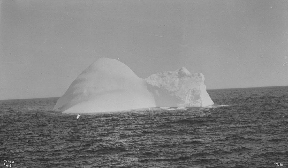 Photo noir et blanc d'un iceberg arrondi avec affleurement en bloc au milieu de l'océan.