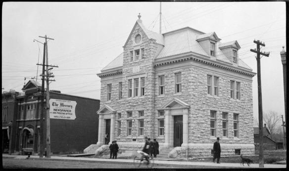 Photo noir et blanc d'un gros bâtiment en pierres. Des hommes marchent devant lui sur le trottoir. Une affiche placée sur le bâtiment à côté dit « The Mercury Newspaper ».