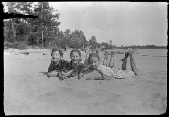 Photo noir et blanc de trois filles allongées côte à côte sur le ventre, dans le sable.