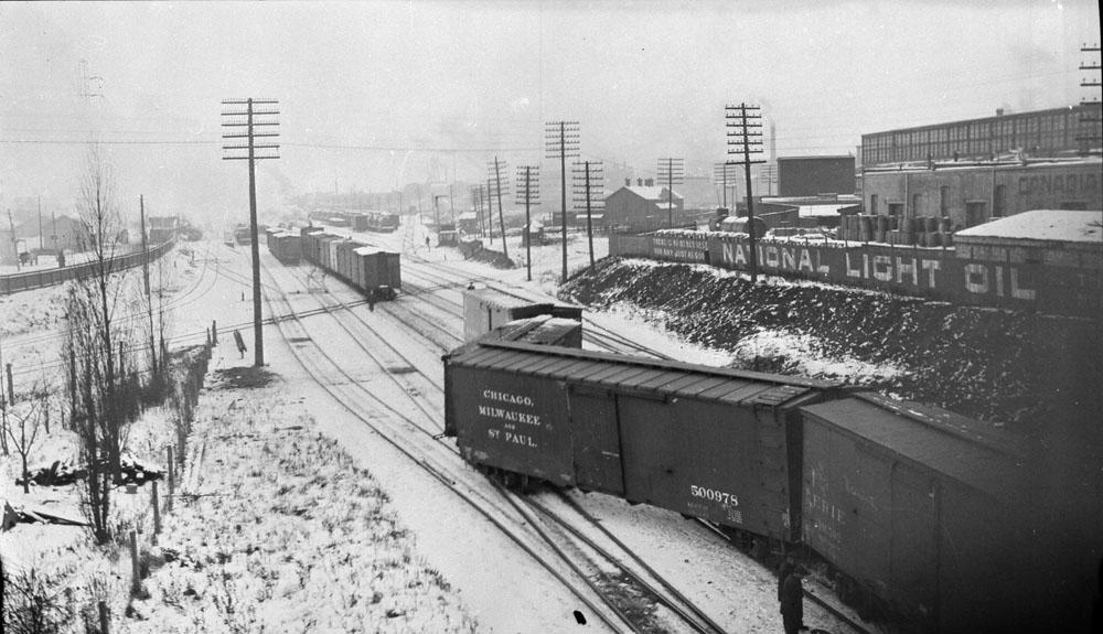 Photo noir et blanc montrant un déraillement dans la gare de triage. Le sol est couvert de neige et une ville se trouve à l'arrière-plan.