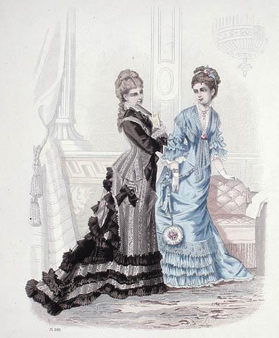 Gravure en couleur de deux femmes debout dans un salon. L'une porte une robe bleue avec des ruches sur les manches et l'ourlet. L'autre porte une robe ornée de rayures noires et grises, avec une longue tournure et des ruches le long de l'ourlet.