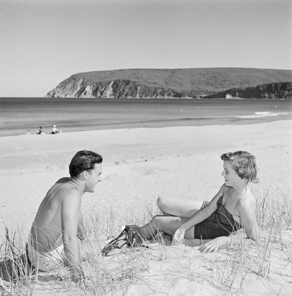 Photo noir et blanc d'un homme et d'une femme souriants assis sur le sable, face-à-face.