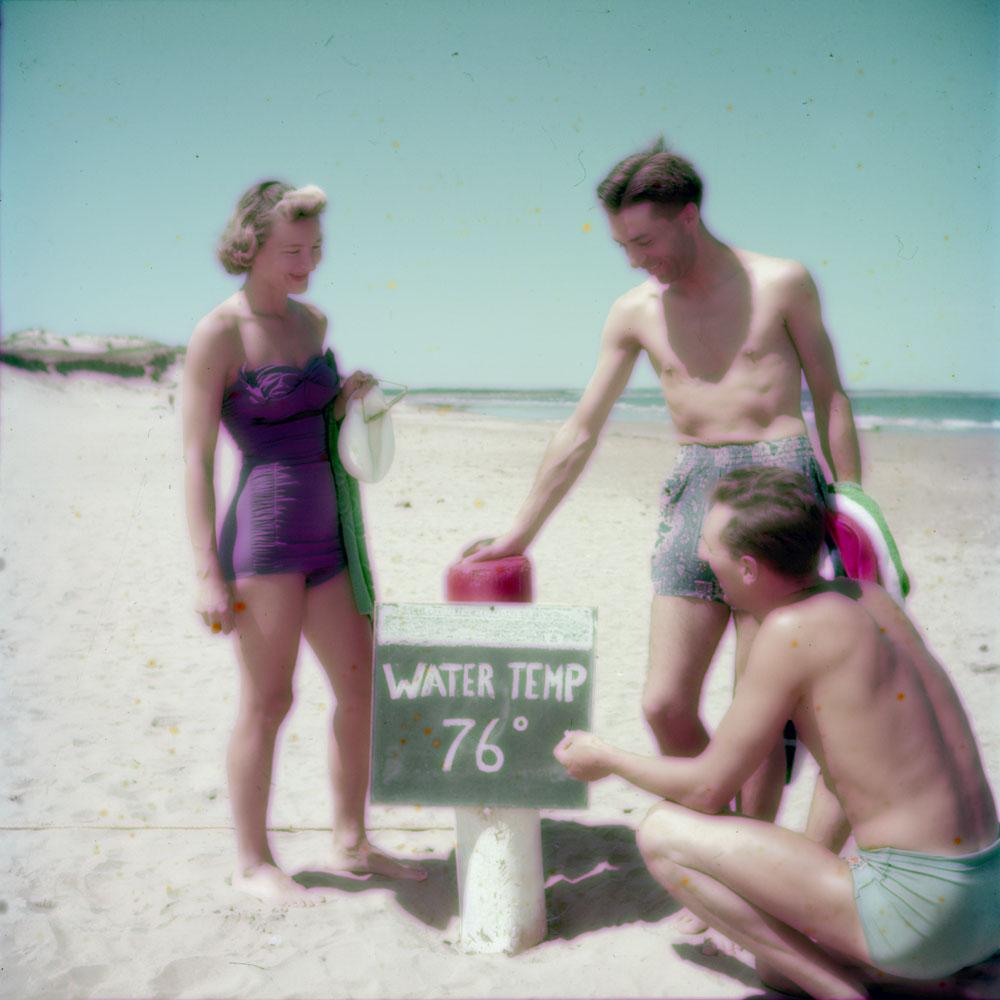 Photo couleur d'une femme et de deux hommes; un des hommes est accroupi et inscrit à la craie la température de l'eau sur une pancarte, soit 76 degrés Fahrenheit.