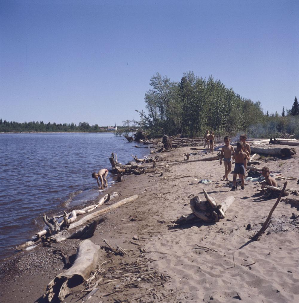 Photo couleur d'un groupe de garçons jouant sur la plage près d'un lac.