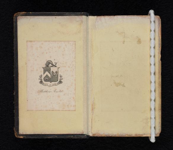 Livre ouvert montrant l'intérieur de la page couverture. Collé sur le côté gauche, on aperçoit l'ex-libris de Matthew Arnold. La page de droite est vierge et retenue par un poids.