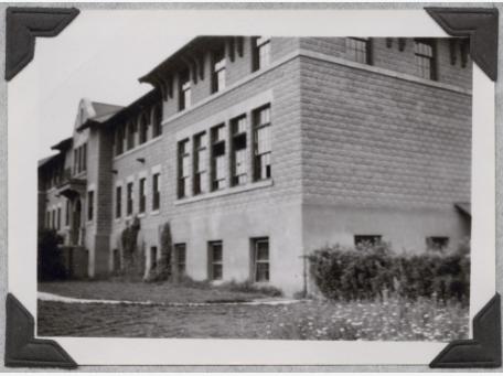 Photo noir et blanc légèrement floue, montrant le côté et la façade d'un bâtiment avec l'entrée principale.